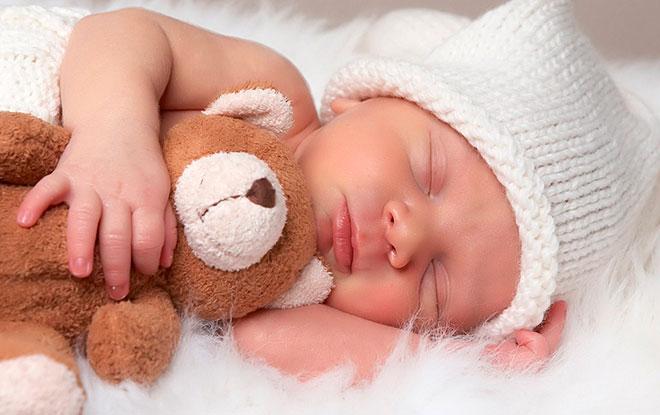 новорожденный ребенок спит с плюшевым мишкой