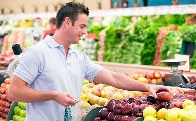 мужчина покупает фрукты