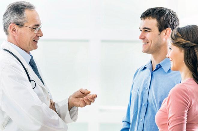 доктор разговаривает с семейной парой