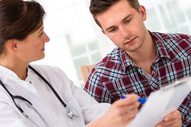 женщина врач и мужчина смотрят результаты анализов