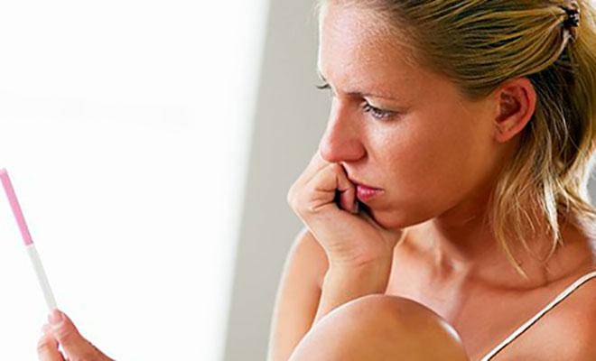 девушка смотрит на тест на беременность