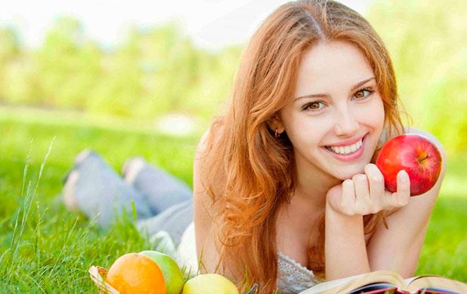 счастливая и здоровая девушка лежит на траве и ест фрукты