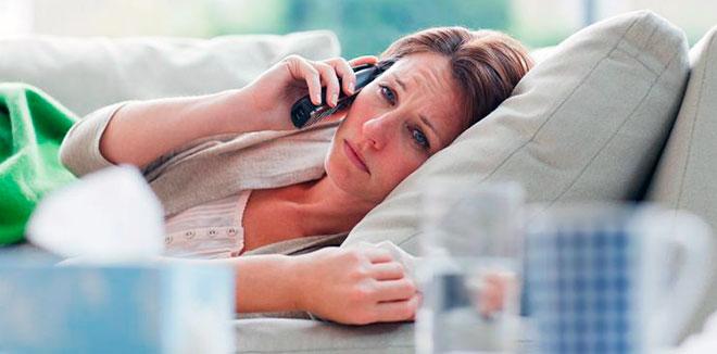 больная женщина звонит своему врачу лежа на диване