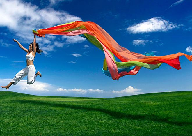 девушка бежит по лугу с красивой тканью в виде радуги