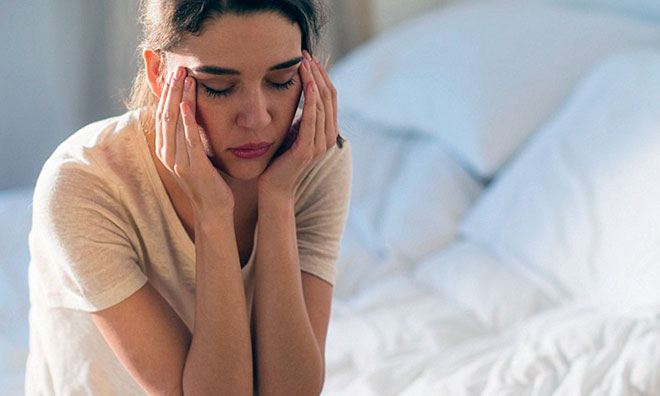 девушка сидит на кровати и плохо себя чувствует
