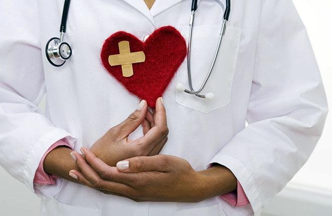 женщина врач держит плюшевое сердце