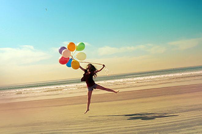 девушка на солнечном пляже с шариками