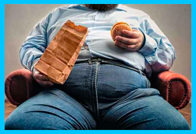 толстый мужчина ест гамбургер