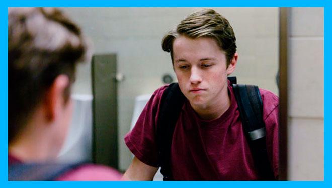 грустный подросток смотрит в зеркало на себя