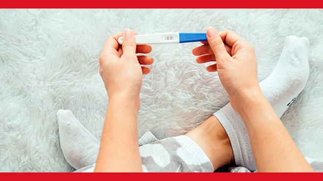 девушка держит тест на беременность с двумя полосками