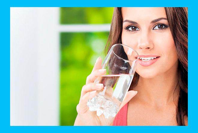 девушка пьет воду из стакана дома