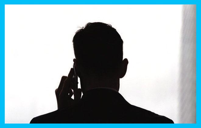 мошенник говорит по телефону с жертвой