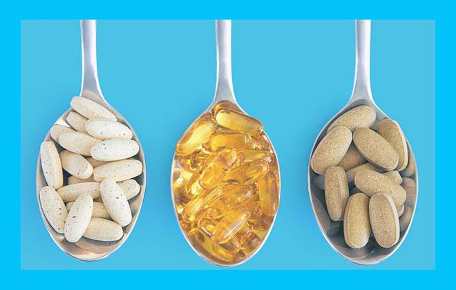 капсулы витаминных комплексов на трех ложках