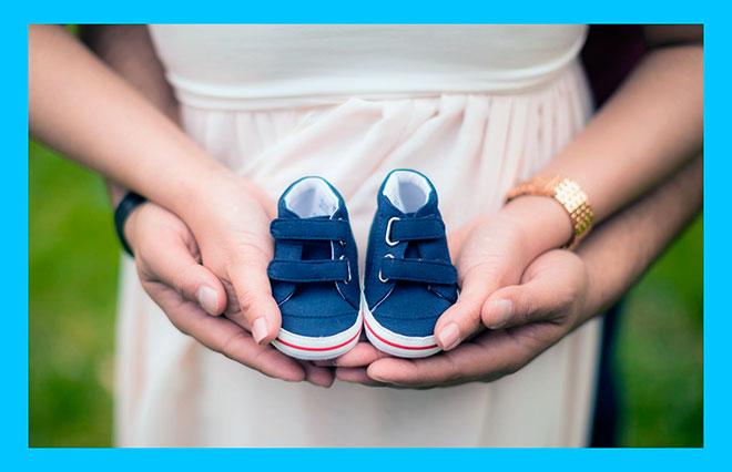 мужчина и женщина держат маленькие ботиночки на ладонях