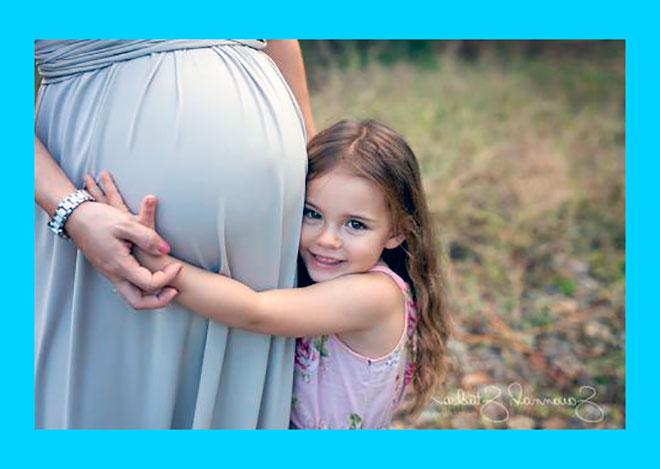 маленькая девочка обнимает большой живот беременной мамы
