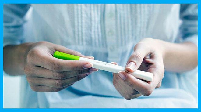 девушка держит в руках тест на беременность
