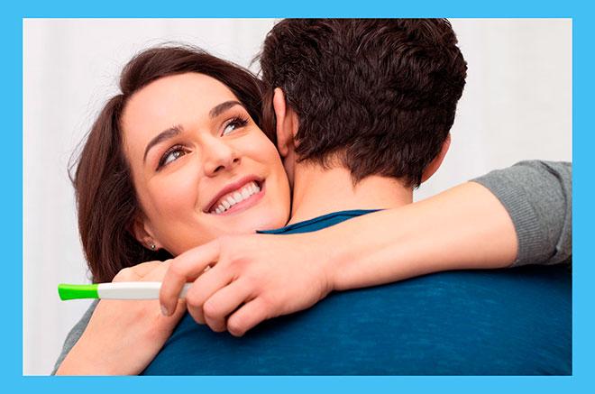 радостная женщина с тестом на беременность обнимает мужчину