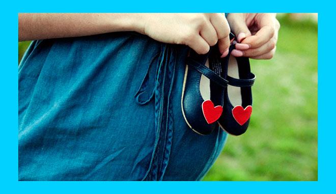 беременная девушка держит в руках ботиночки с сердечками