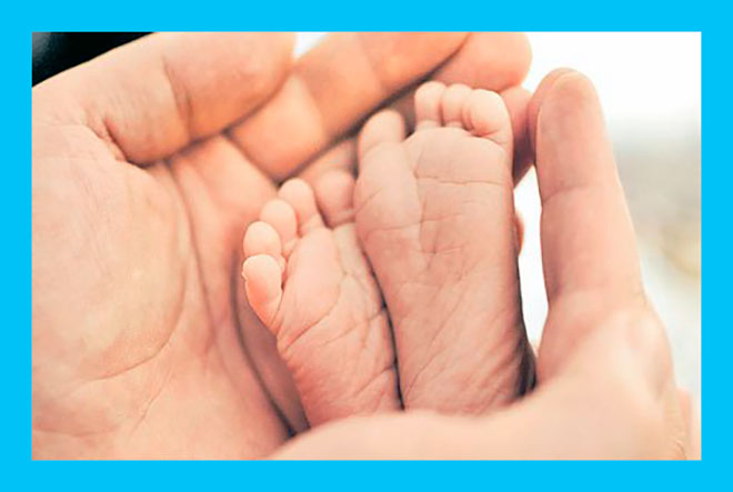 мама трогает ножки новорожденного малыша
