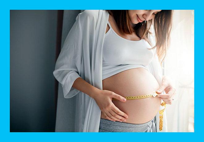 беременная женщина измеряет свой большой живот метром