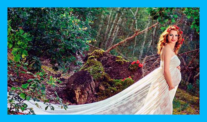 красивая фотография беременной женщины в белом длинном платье в лесу