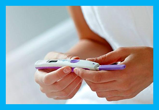 женщина держит в руках тест на беременность