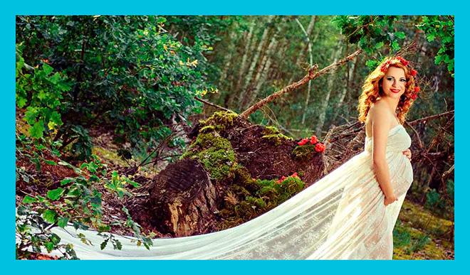беременная женщина в длинном белом платье в летнем лесу