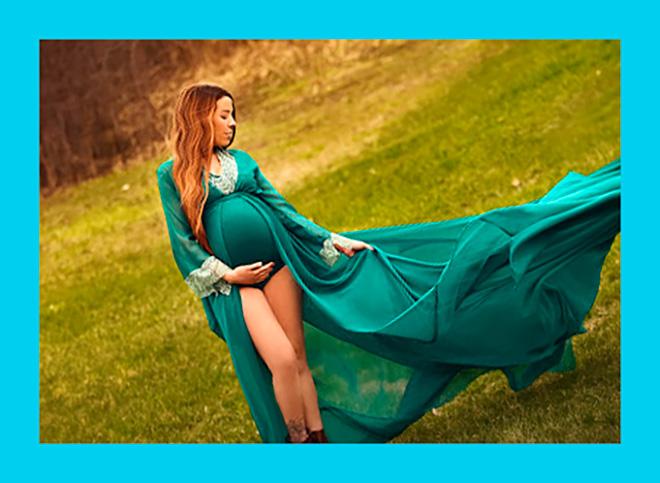 беременная женщина в шикарном зеленом платье идет по полю