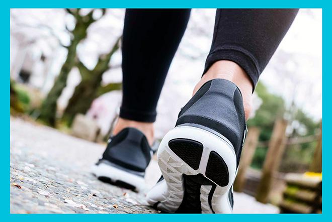 женщина в кроссовках и леггинсах идет быстрым шагом по парку