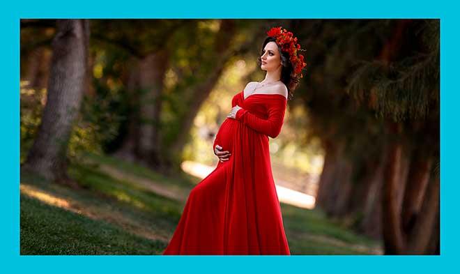 красивая беременная женщина в длинном красном платье в лесу